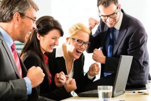 group of people cheering about meeting business goals